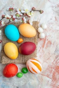 Bovenaanzicht gekleurde beschilderde eieren op witte achtergrond suiker kleurrijk zoet voorjaarsvakantie sierlijk