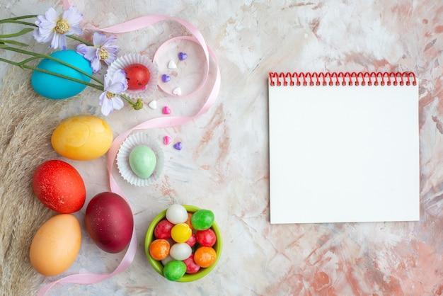 Bovenaanzicht gekleurde beschilderde eieren op witte achtergrond suiker kleurrijke lente sierlijke novruz sweet