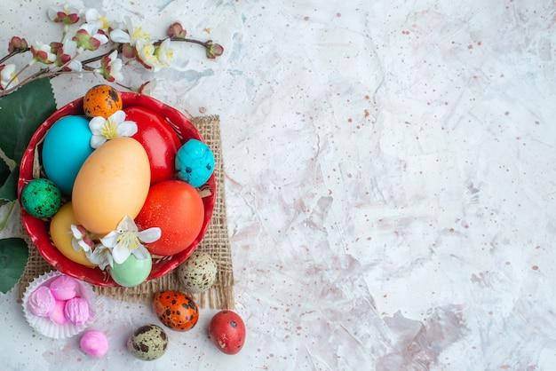 Bovenaanzicht gekleurde beschilderde eieren op witte achtergrond suiker kleurrijke lente vakantie sierlijke novruz zoete vrije ruimte