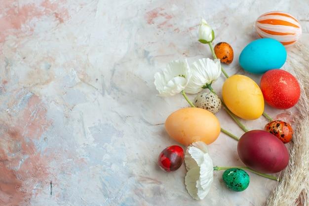 Bovenaanzicht gekleurde beschilderde eieren op witte achtergrond suiker kleurrijke novruz zoete voorjaarsvakantie