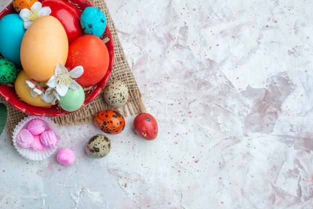 Bovenaanzicht gekleurde beschilderde eieren op witte achtergrond suiker lente vakantie sierlijke novruz zoete kleurrijke vrije plaats