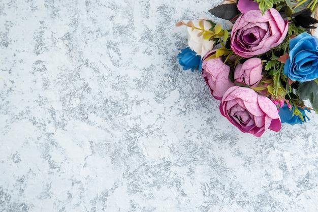 Bovenaanzicht gekleurde bloemen op tafel met kopie plaats