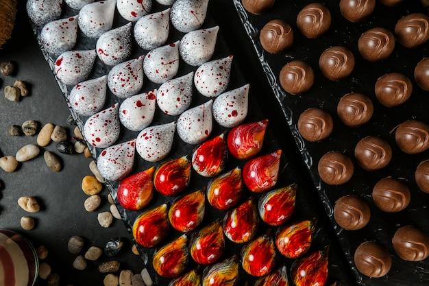 Bovenaanzicht gekleurde decoratieve chocolaatjes op een stand met stenen op een zwarte achtergrond