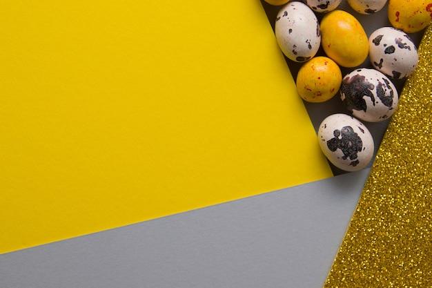Bovenaanzicht gekleurde eieren en papieren achtergronden in trendy kleuren voor pasen met kopie ruimte