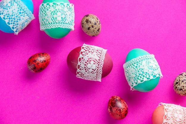 Bovenaanzicht gekleurde eieren op roze achtergrond kleurrijke voorjaarsvakantie etnische sierlijke novruz
