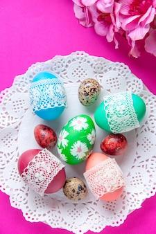 Bovenaanzicht gekleurde eieren op roze achtergrond sierlijke novruz vakantie etnische concept lente
