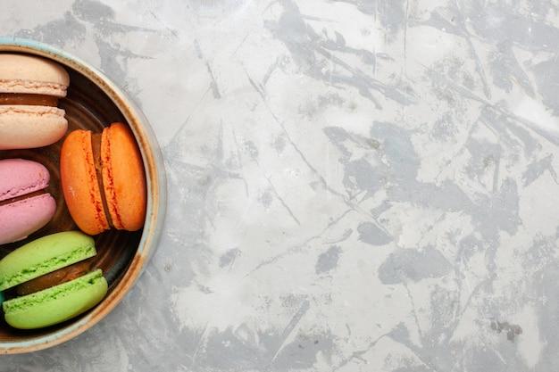 Bovenaanzicht gekleurde franse macarons heerlijke kleine cakes op wit bureau