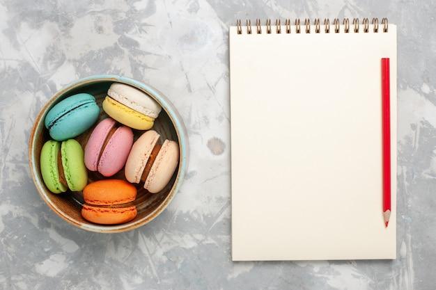 Bovenaanzicht gekleurde franse macarons heerlijke kleine cakes op witte vloer zoete cake suiker biscuit taart thee cookie