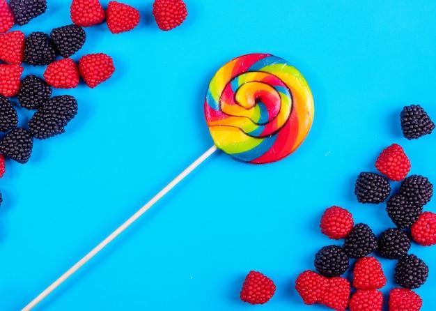 Bovenaanzicht gekleurde ijspegel met marmelade in de vorm van frambozen en bramen op een blauwe achtergrond
