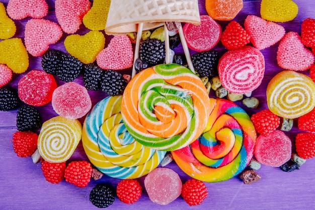 Bovenaanzicht gekleurde ijspegels met kleurrijke marmelade van verschillende vormen en wafel hoorns op een paarse achtergrond