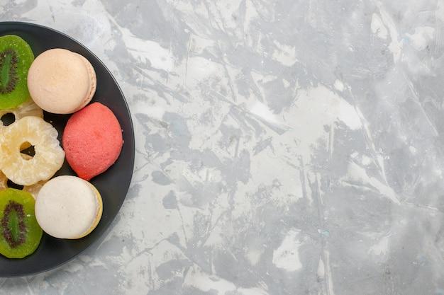 Bovenaanzicht gekleurde kleine cakes met gedroogde ananasringen op het lichtwitte oppervlak