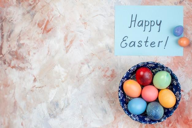 Bovenaanzicht gekleurde paaseieren binnen blauwe plaat op lichte achtergrond vakantie sierlijke concept horizontale kleurrijke lente