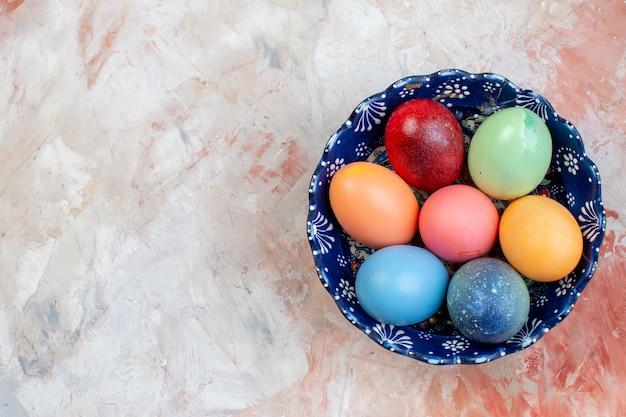 Bovenaanzicht gekleurde paaseieren binnen blauwe plaat op lichte achtergrond vakantie sierlijke lente concept horizontaal kleurrijk