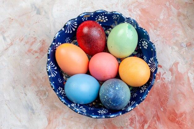 Bovenaanzicht gekleurde paaseieren binnen blauwe plaat op lichte achtergrond vakantie sierlijke lente pasen concept horizontaal kleurrijk