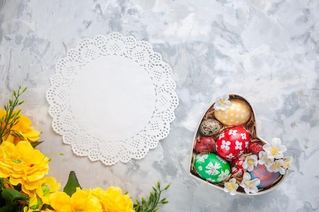 Bovenaanzicht gekleurde paaseieren in hartvormige doos met gele bloemen wit oppervlak lente vakantie pasen sierlijke kleurrijke concept