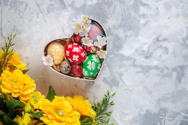 Bovenaanzicht gekleurde paaseieren in hartvormige doos met gele bloemen wit oppervlak vakantie pasen lente versierd kleurrijk