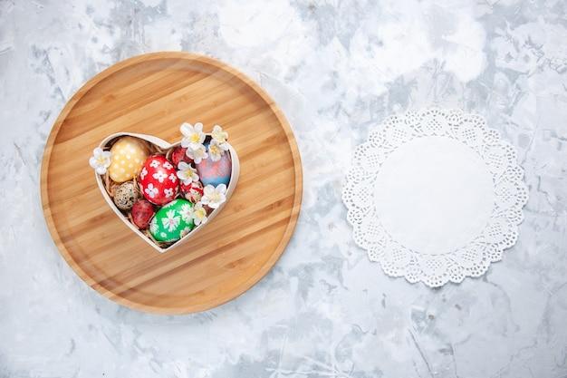 Bovenaanzicht gekleurde paaseieren in hartvormige doos op snijplank wit oppervlak concept kleurrijke vakantie verf sierlijke lente vrije plaats