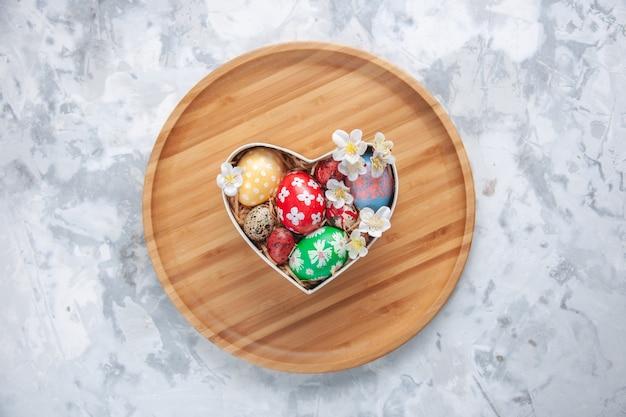 Bovenaanzicht gekleurde paaseieren in hartvormige doos op snijplank wit oppervlak concept kleurrijke vakantie verf sierlijke lente