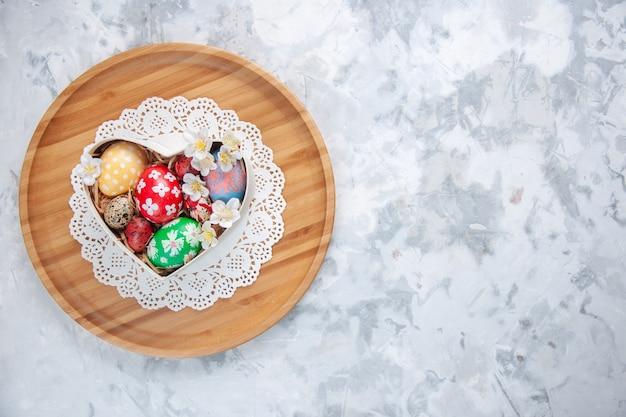 Bovenaanzicht gekleurde paaseieren in hartvormige doos op snijplank wit oppervlak concept kleurrijke verf sierlijke lente