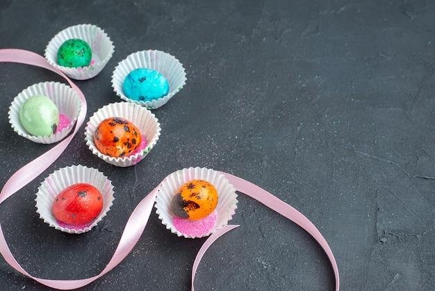 Bovenaanzicht gekleurde paaseieren in kleine cakevormen op een donkere ondergrond