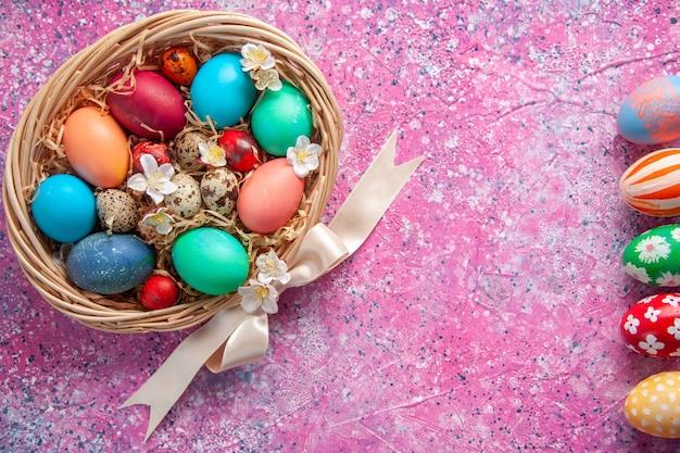 Bovenaanzicht gekleurde paaseieren in mand op roze oppervlak lente kleur kleurrijk concept sierlijke paasvakantie