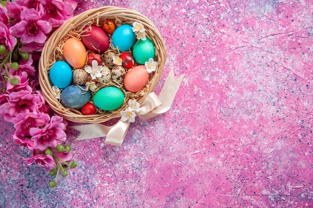 Bovenaanzicht gekleurde paaseieren in mand op roze oppervlak lente kleurrijk concept paasvakantie sierlijke kleur