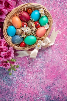 Bovenaanzicht gekleurde paaseieren in mand op roze oppervlak lente kleurrijk concept paasvakantie sierlijke kleuren