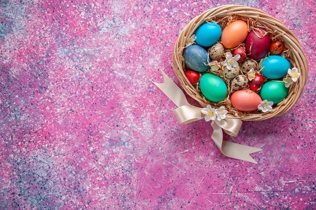 Bovenaanzicht gekleurde paaseieren in mand op roze oppervlak lente kleurrijk versierd concept paasvakantie