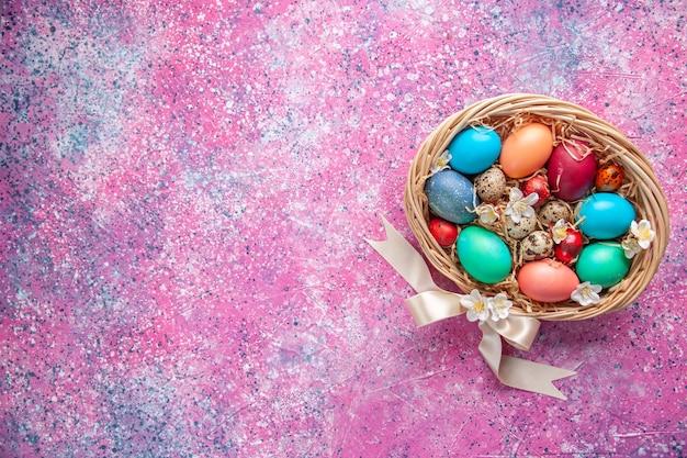 Bovenaanzicht gekleurde paaseieren in mand op roze oppervlak lente kleurrijke bloem sierlijke concept paasvakantie