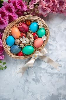 Bovenaanzicht gekleurde paaseieren in mand op wit oppervlak lente kleurrijke bloem vakantie concept pasen