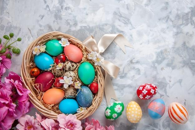 Bovenaanzicht gekleurde paaseieren in mand op wit oppervlak lente kleurrijke bloem vakantie sierlijke concept pasen