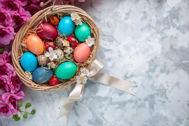 Bovenaanzicht gekleurde paaseieren in mand op wit oppervlak lente kleurrijke bloem vakantie sierlijke pasen