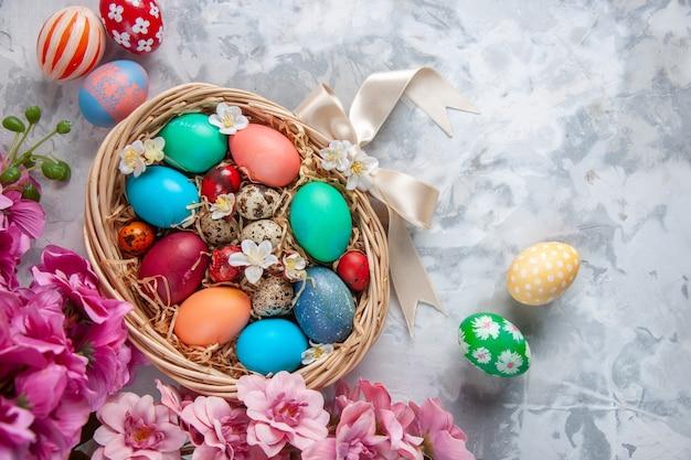 Bovenaanzicht gekleurde paaseieren in mand op wit oppervlak lente kleurrijke paasbloemen vakantie sierlijke concept