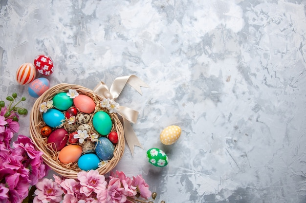 Bovenaanzicht gekleurde paaseieren in mand op wit oppervlak lente kleurrijke paasvakantie sierlijke concept