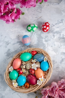 Bovenaanzicht gekleurde paaseieren in mand op wit oppervlak lente kleurrijke sierlijke pasen concept bloem vakantie