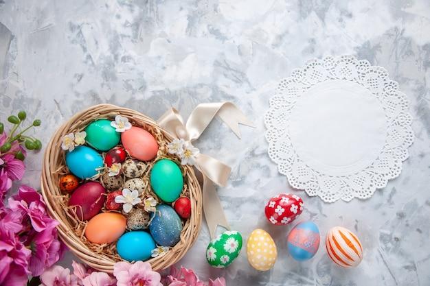 Bovenaanzicht gekleurde paaseieren in mand op wit oppervlak lente kleurrijke vakantie sierlijke concept pasen