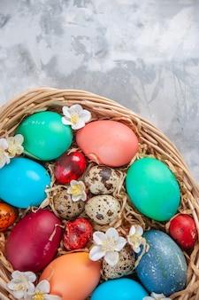 Bovenaanzicht gekleurde paaseieren in mand op wit oppervlak lente pasen sierlijke kleurrijke concept vakantie