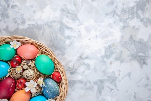 Bovenaanzicht gekleurde paaseieren in mand op wit oppervlak lente vakantie pasen sierlijke kleurrijke concept gratis plaats