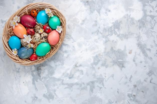 Bovenaanzicht gekleurde paaseieren in mand op wit oppervlak lente vakantie pasen sierlijke kleurrijke concept vrije ruimte