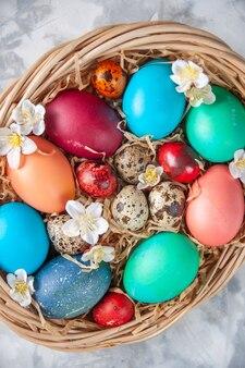 Bovenaanzicht gekleurde paaseieren in mand op wit oppervlak lente vakantie pasen sierlijke kleurrijke concept