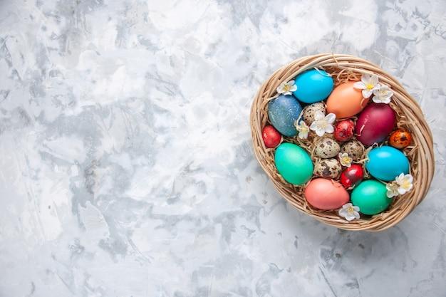 Bovenaanzicht gekleurde paaseieren in mand op wit oppervlak voorjaarsvakantie pasen sierlijke kleurrijke