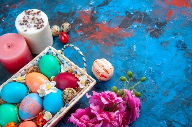 Bovenaanzicht gekleurde paaseieren in schattige doos op blauw oppervlak