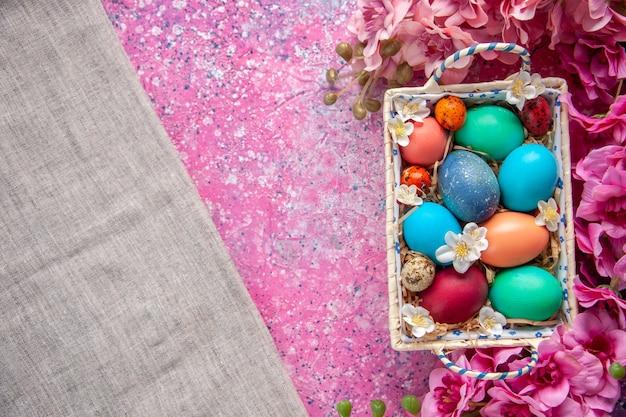Bovenaanzicht gekleurde paaseieren in schattige doos op roze oppervlak kleur lente concept paasvakantie sierlijke kleurrijk