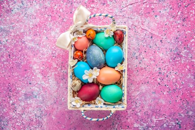 Bovenaanzicht gekleurde paaseieren in schattige doos op roze oppervlak lente kleur kleurrijk paasconcept sierlijk