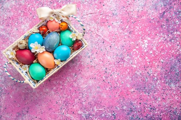 Bovenaanzicht gekleurde paaseieren in schattige doos op roze oppervlak lente kleur kleurrijk paasvakantie concept sierlijke vrije plaats