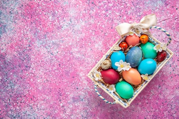 Bovenaanzicht gekleurde paaseieren in schattige doos op roze oppervlak lente kleur kleurrijk paasvakantie concept sierlijke vrije ruimte