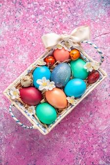 Bovenaanzicht gekleurde paaseieren in schattige doos op roze oppervlak lente kleur kleurrijk paasvakantie concept