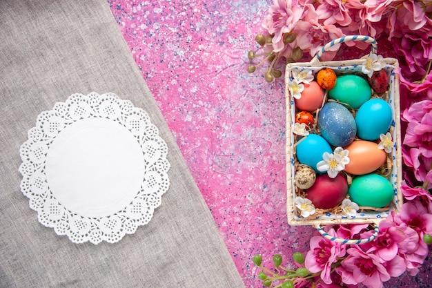 Bovenaanzicht gekleurde paaseieren in schattige doos op roze oppervlak vakantie kleur lente pasen sierlijke kleurrijke concept