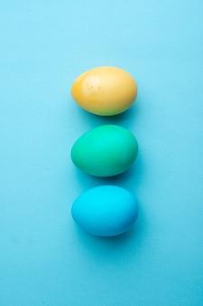 Bovenaanzicht gekleurde paaseieren op blauw oppervlak