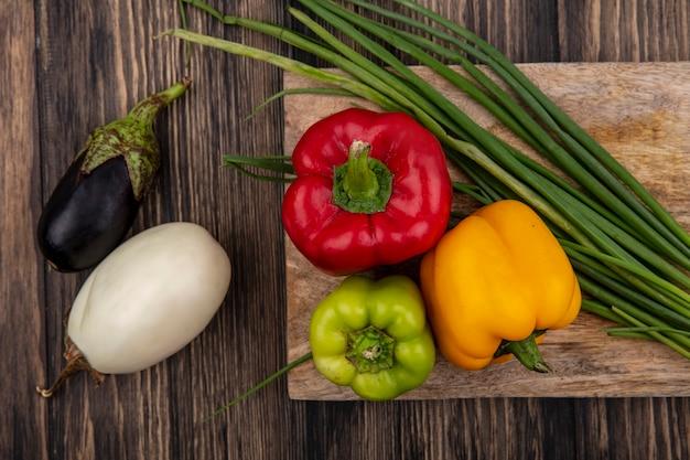 Bovenaanzicht gekleurde paprika met groene uien op een snijplank met witte en zwarte aubergine op houten achtergrond